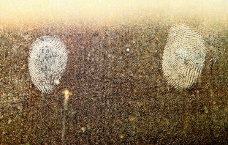 imagem de duas digitais impressas em um vidro sujo