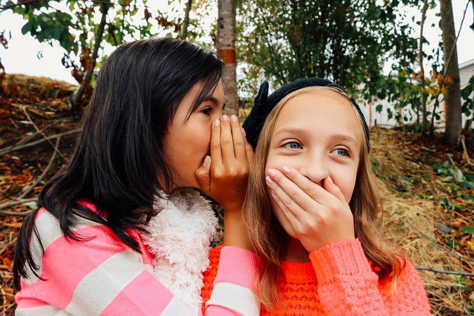 Uma criança está contando algo no ouvido de outra, que leva a mão à boca e franze os olhos.