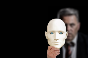 Um homem de terno segura uma máscara branca