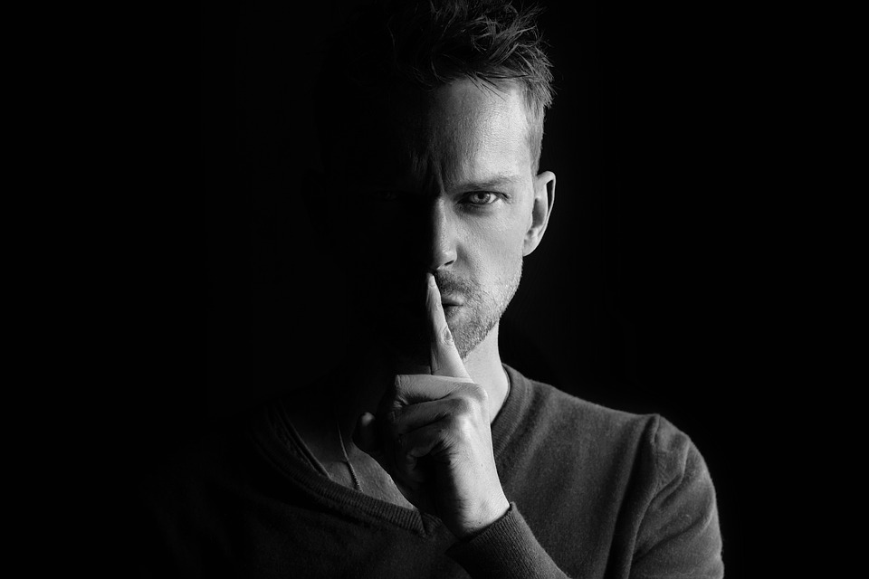 Um homem em um fundo escuro leva o dedo indicador à frente da boca.