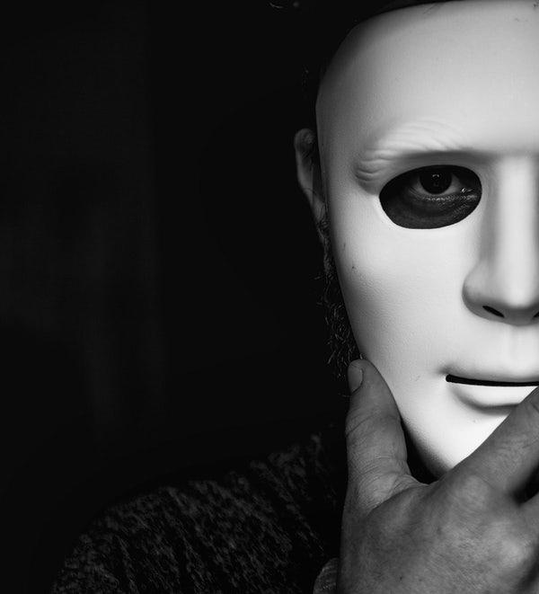 Uma pessoa em um ambiente escuro segura uma máscara branca na frente do rosto