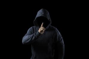 Uma pessoa encapuzada em um ambiente escuto está fazendo o gesto de pedir silêncio.