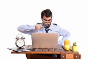 Um homem usando camisa social e gravata está apontando uma lupa para o computador em sua mesa.