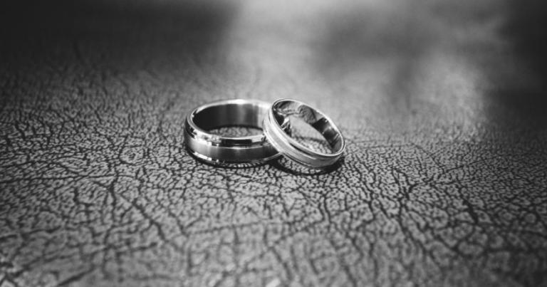 foto em preto e branco de duas alianças em um chão craquelado