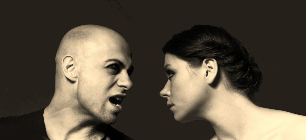 Homem e mulher se olhando com expressões irritadas