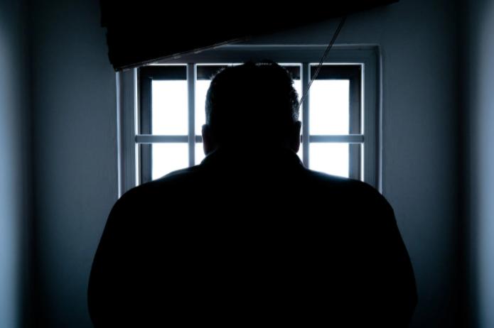 silhueta de homem em frente a uma janela com grades