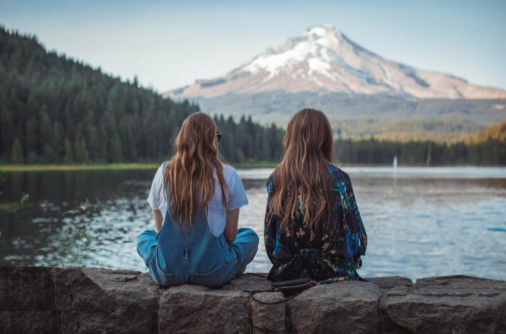duas mulheres sentadas em um muro de pedra olhando para um lago