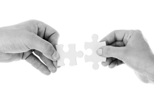 imagem com fundo branco de duas mãos segurando peças de quebra cabeça tentando encaixá-las