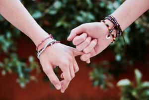 imagem ampliada de duas pessoas segurando o dedo mindinho um do outro com algumas plantas de fundo