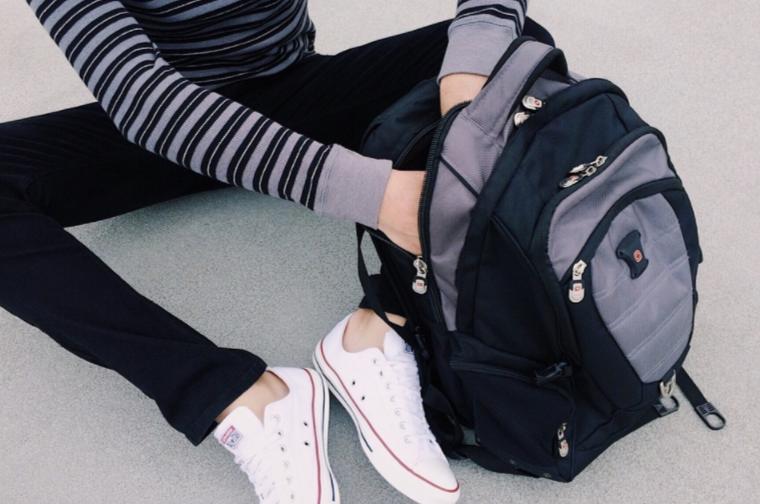 Adescente guardando algum objeto dentro da mochila.