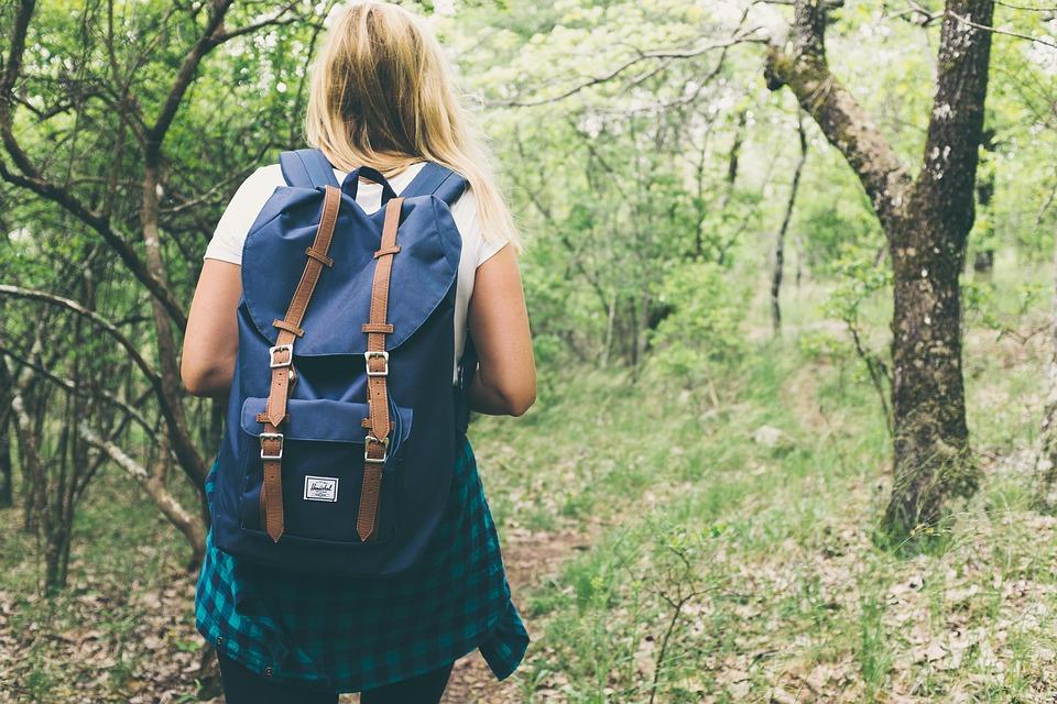 Adolescente com mochila nas costas andando em uma área verde.