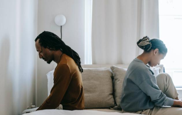 casal de costas um para o outro sobre a cama, depois de mulher comprovar a infidelidade do marido