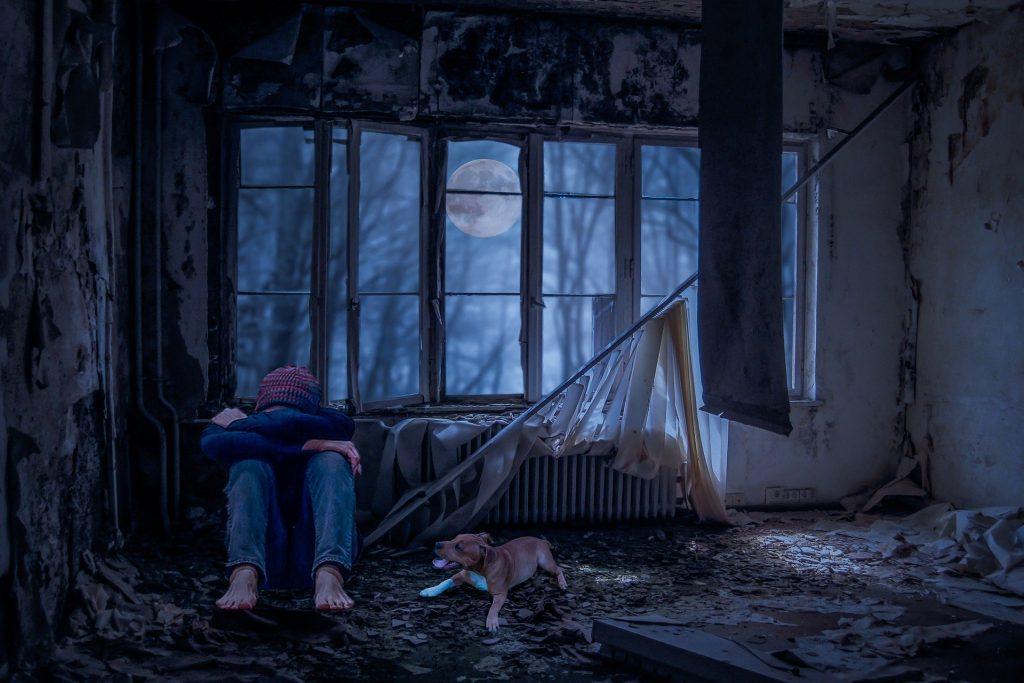 Adolescente abraçando os joelhos e cabisbaixo em uma cabana abandonada, com um cachorro ao lado