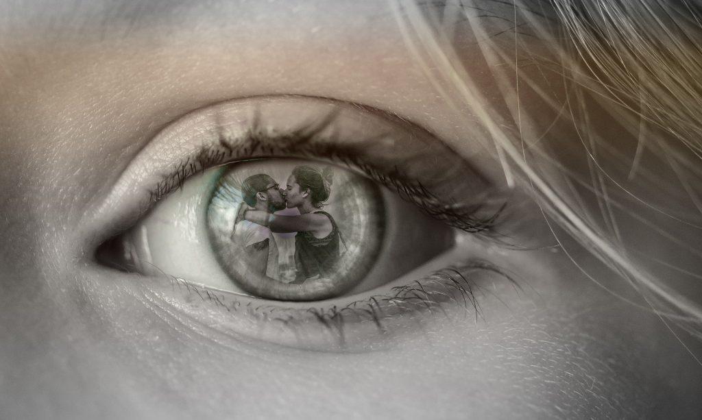 imagem de um olho feminino refletindo um casal se beijando