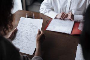 Mulher segurando um documento acima de uma mesa. Em frente a ela, do outro lado da mesa, um homem está sentado e olhando para outro documento.