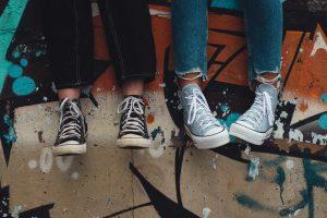 quatro pernas e pés encostados em uma parede colorida grafitada, todos com calças jeans e all star: capa do conteúdo de comportamentos típicos da adolescência